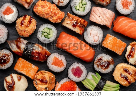 Assorted sushi nigiri and maki big set on slate. A variety of Japanese sushi with tuna, crab, salmon, eel and rolls. Top view