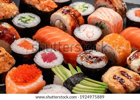 Assorted sushi nigiri and maki set on slate. A variety of Japanese sushi with tuna, crab, salmon, eel and rolls.
