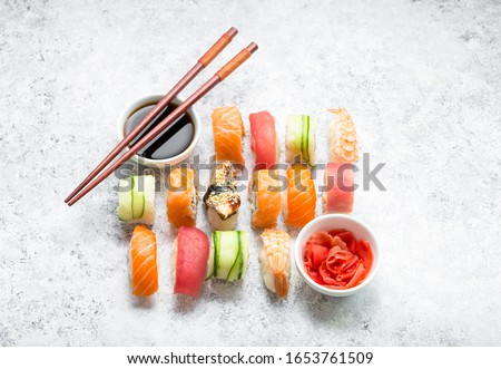 Assorted sushi set on white concrete background. Japanese sushi, rolls, soy sauce, ginger, chopsticks. Top view. Sushi nigiri. Japanese dinner/lunch. Different sushi mixed. Japanese food concept