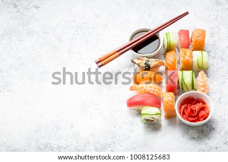 Assorted sushi set on white concrete background. Space for text. Japanese sushi, rolls, soy sauce, ginger, chopsticks. Top view. Sushi nigiri. Japanese dinner/lunch. Food frame. Different sushi mixed