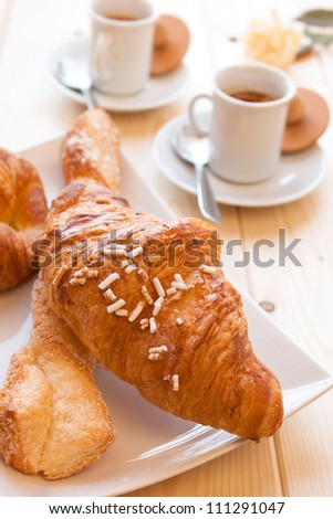 Assorted sweet brioches on dish and hot coffee morning breakfast