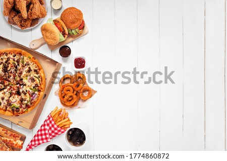 Assorted take out or delivery foods. Side border. Pizza, hamburgers, fried chicken and sides. Above view on a white wood background with copy space. Foto stock ©
