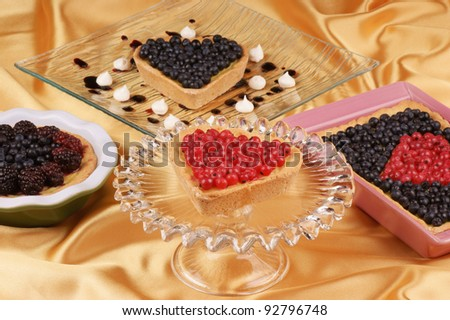Assorted tarts with blueberries, redcurrants and raspberries. Selective focus, shallow DOF - stock photo