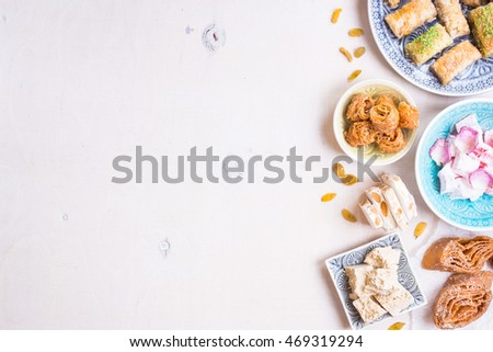 Assorted traditional eastern desserts on white background. Arabian sweets on wooden table. Baklava, halva, rahat lokum, sherbet, nuts, dates, kadayif on plates. Space for text. Selective focus