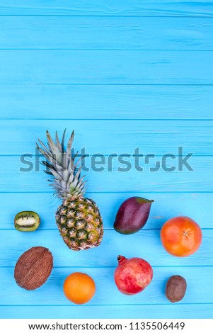 Assorted tropical fruits, top view. Set of exotic fruits over blue wooden background with copy space. Healthy and nutritious fruits. #1135506449