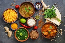 Assorted various Indian food on a dark rustic background. Traditional Indian dishes - Chicken tikka masala, palak paneer, saffron rice, lentil soup, pita bread and spices. Top view, flat lay