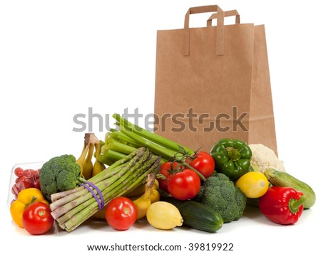 Assorted vegetables and fruits including asparagus, celery, tomatoes, peppers, bananas, lemons, cauliflower, cherry tomatoes, broccoli, cucumber and squash with a grocery sack on a white background
