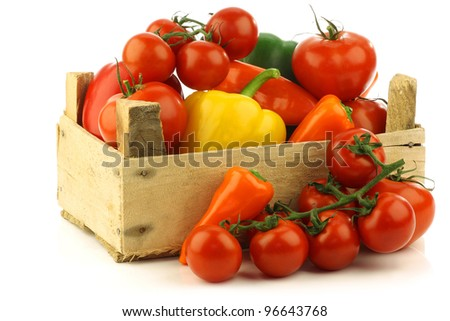assorted vegetables in a wooden crate on a white background