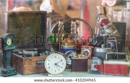 Photo of  Assorted vintage items, clocks, cameras, flasks, sextant, lamps behind shop window.