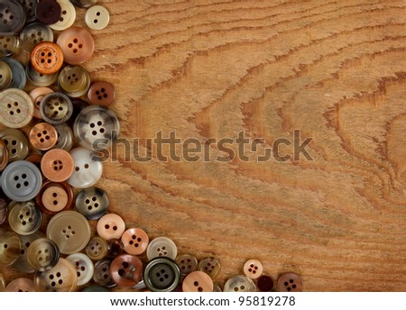 Assorted vintage sewing buttons on a wooded background, room for copy space