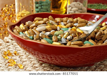 Assorted vitamins and nutritional supplements in decorative bowl with serving spoon.  Glass containers filled with vitamins and oils in the background.  Conceptual image for nutritional care.