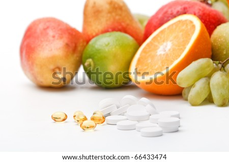 Assorted wet fresh fruits and pills on white background