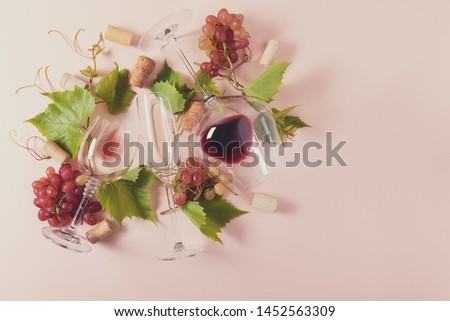Assorted wineglasses with red, rose and white wine, grape, leaves and cork lying on pink background. Wine degustation concept. Flat lay. Top view. Copy space. Toned #1452563309