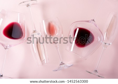 Assorted wineglasses with red, rose and white wine lying on pink background. Wine degustation concept. Flat lay. Top view. Copy space #1452563300