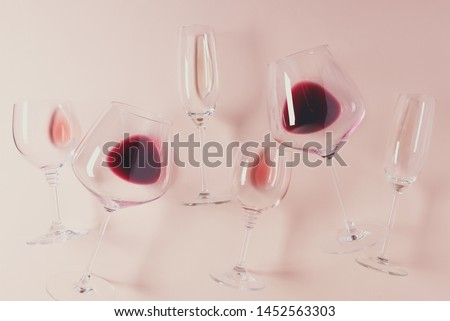 Assorted wineglasses with red, rose and white wine lying on pink background. Wine degustation concept. Flat lay. Top view. Copy space. Toned #1452563303