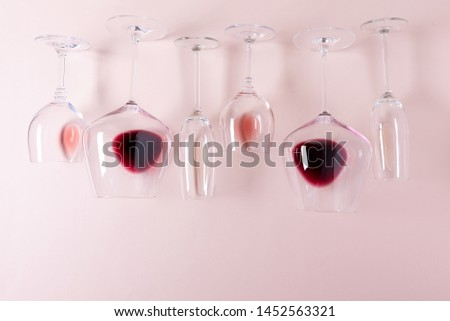 Assorted wineglasses with red, rose and white wine lying top edge on pink background. Wine degustation concept. Flat lay. Top view. Copy space #1452563321