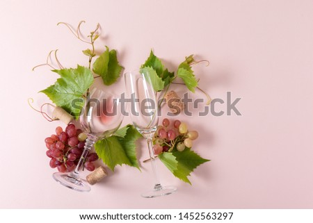 Assorted wineglasses with rose and white wine, grape, leaves and cork lying on pink background. Wine degustation concept. Flat lay. Top view. Copy space #1452563297