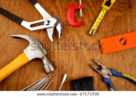 Assorted work tools on wooden panel