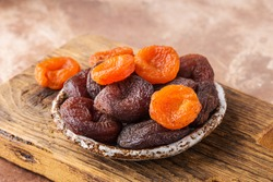 Assortment dried apricots in ceramic plate on wooden board, brown background, healthy concept.