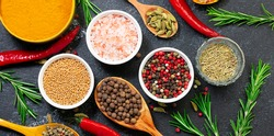 Assortment of aromatic organic spices and herbs on black rustic background close up. Healthy food concept.