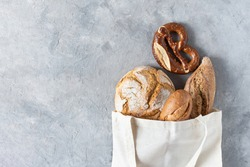 Assortment of baked bread and buns in white fabric shopping bag on grey concrete background top view. Healthy organic bread. Eco-shopping concept.