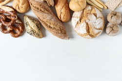 Assortment of baked bread and buns on white wooden background top view. Healthy organic bread.