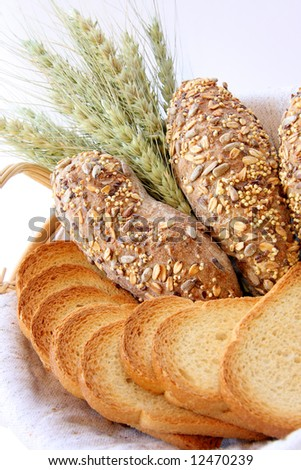 Assortment of baked bread with wheat isolated on white background