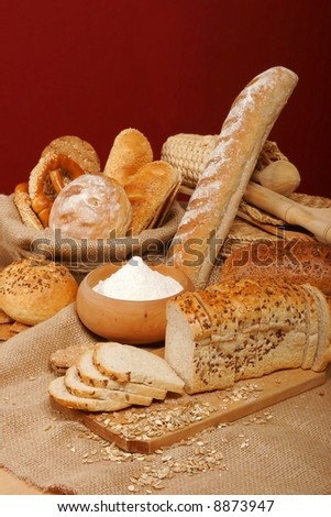 Assortment of baked breads with a bowl of flour on red background