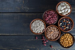 Assortment of beans on black wooden background. Soybean, red kidney bean, black bean,white bean, red bean and brown pinto beans