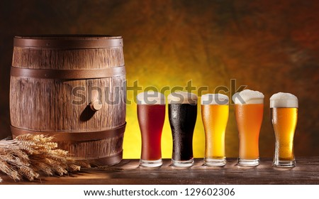 Assortment of beer glasses with a wooden barrel. Background - dark yellow gradient.