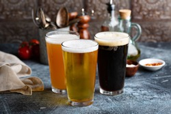 Assortment of beer in tall glasses ina rustic setting