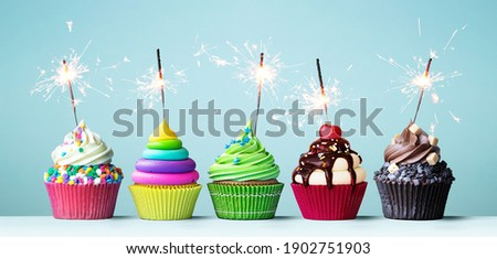Assortment of brightly colored celebration cupcakes decorated with sparklers for a birthday party