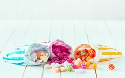 Assortment of candies in three striped decorated bags scattered over a white wooden table
