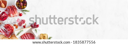 Assortment of cheese and meat appetizers. Overhead view corner border on a white marble banner background with copy space. Stok fotoğraf ©