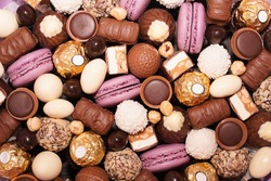 Assortment of chocolate colourful, festive sweets candy macaroons and nuts. Sweet candy background. mix of chocolate candies, top view. Choco lilac background.