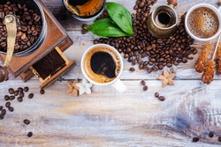 Assortment of coffee in mugs and cups, coffee grinder, jesve and roasted coffee beans on wooden background. Coffee time concept. Copy space