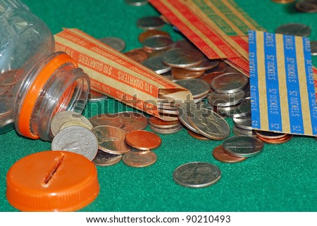 Assortment of coins poured from homemade bank to be sorted and rolled in paper rollers.