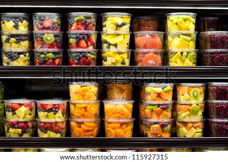 Assortment of cut fruit in containers on display for sale - stock photo
