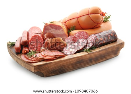 Assortment of delicious deli meats on wooden board, isolated on white
