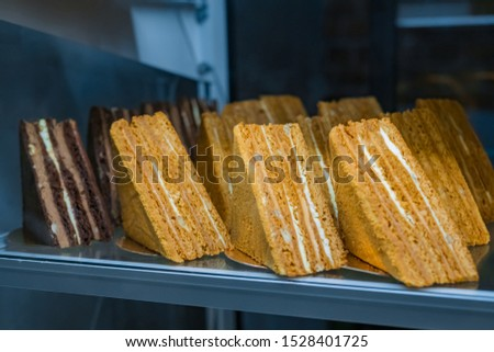 Assortment of delicious fresh layered chocolate and honey cake pieces with cream and nuts for sale on counter of shop, grocery, market, cafe or bakery. Dessert, sweet food and confectionery concept
