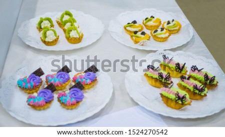 Assortment of delicious fresh shortcrust tart cakes with cream and fruits for sale on white plate at cuisine of restaurant, cafe. Dessert, culinary, sweet food and confectionery concept