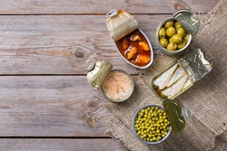 Assortment of different canned preserved vegetables, meat, fish, seafood in tin cans on a wooden table. Non-Perishable goods, food, donations concept. Flat lay top view copy space background