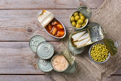 Assortment of different canned preserved vegetables, meat, fish, seafood in tin cans on a wooden table. Non-Perishable goods, food, donations concept. Flat lay top view background