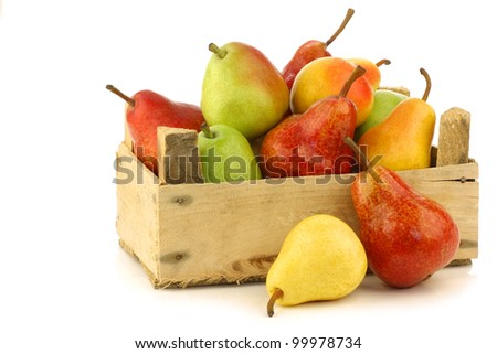 Assortment of different colorful pears in a wooden crate on a white background