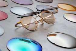 Assortment of different multicolored lenses for eyewear, fashion trendy sunglasses with changeable lenses lying on table in professional optical shop. Optician technician and eyesight concept