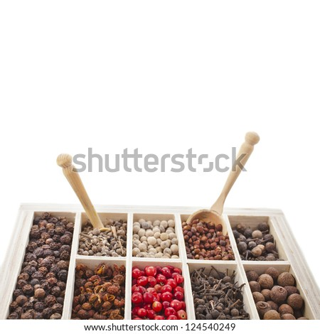 Assortment of different peppercorns in wooden box isolated on white