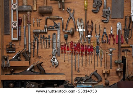 assortment of do it yourself tools hanging in a wooden cupboard against a wall