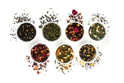 Assortment of dry tea in bowls isolated on white background. Red, fruit, green, black and herbal leaves dried fresh dessert beverage layout. Flat lay style. Top view concept. Healthy, organic drink