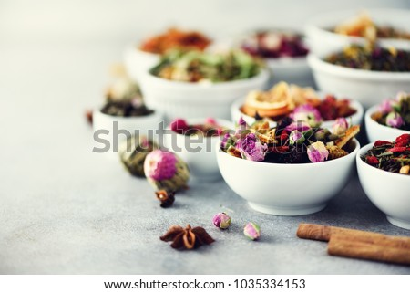 Assortment of dry tea in white bowls. Tea types backgound: green, black, floral, herbal, mint, melissa, ginger, apple, rose, lime tree, fruits, orange, hibiscus, raspberry, cornflower, cranberry.