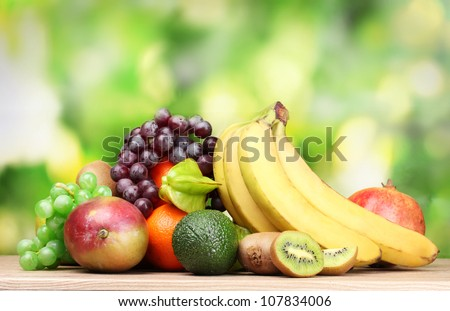 Assortment of exotic fruits on wooden table on green background